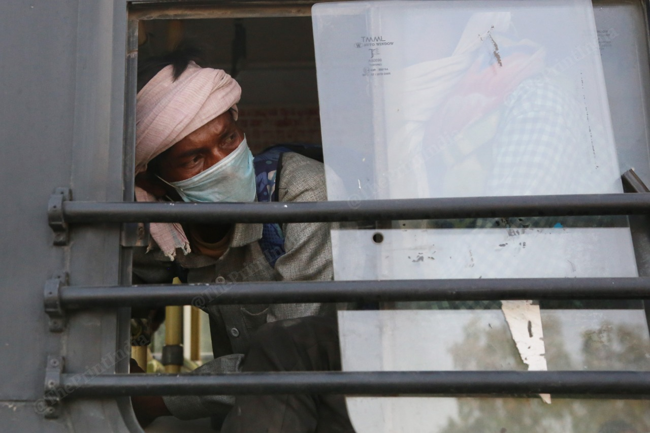 A man looks out the window of a local bus as Delhi Police escorts the homeless to shelter homes. | Photo: Manisha Mondal/ThePrint