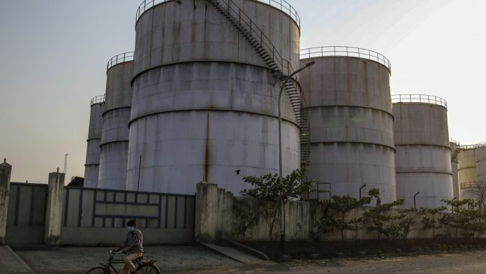 A cyclist rides past oil storage tanks at Jawaharlal Nehru Port, operated by Jawaharlal Nehru Port Trust (JNPT), in Navi Mumbai, Maharashtra | Photographer: Dhiraj Singh | Bloomberg