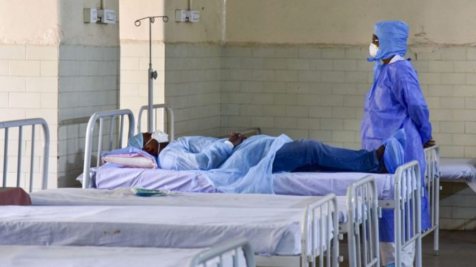 A medic looks on at a patient who has shown positive symptoms for coronavirus at an isolation ward in Hyderabad on 10 March