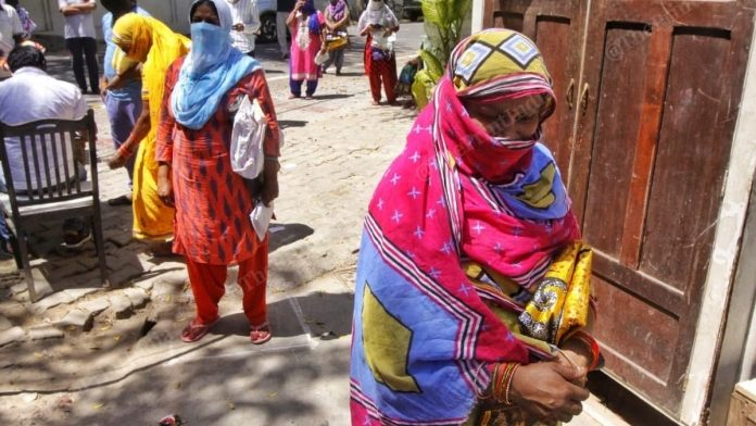 A woman stands in queue outside the Dalibagh ration shop in Lucknow. | Photo: Praveen Jain/ThePrint