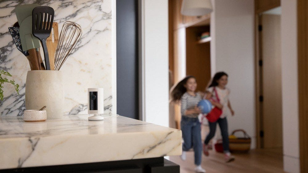 Ring security camera sitting on a kitchen counter as two little girls run by.
