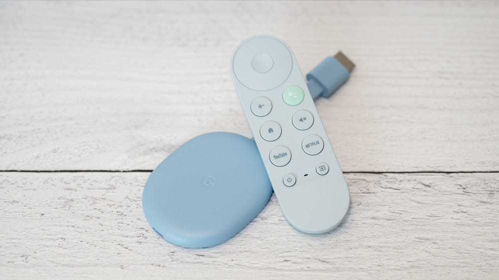 Chromecast with Google TV device and remote control on wooden surface