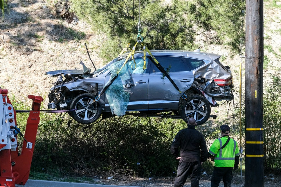 A crane is used to lift the car following a rollover accident involving golfer Tiger Woods
