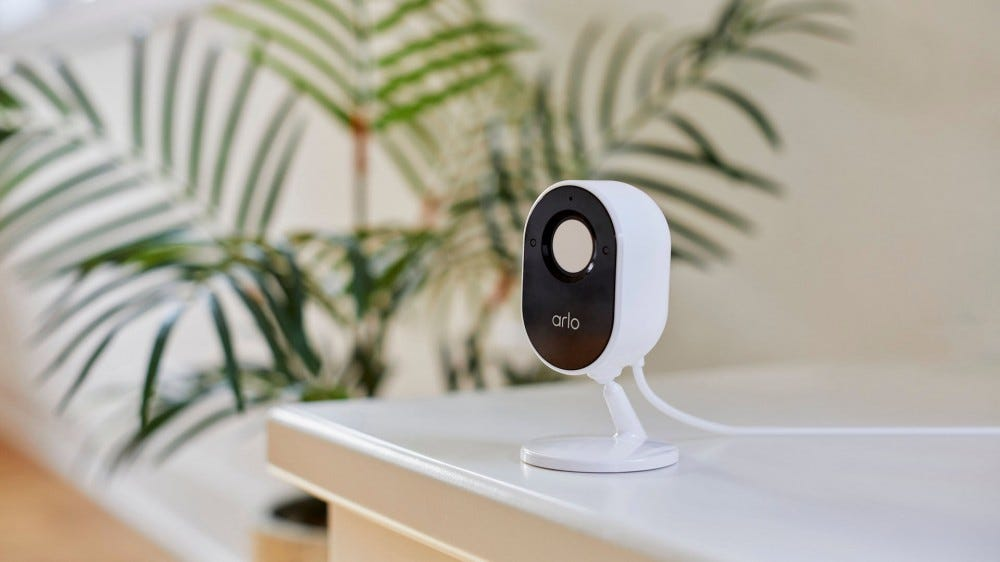 An Arlo Essential Indoor Camera with a built-in shutter covering the lens.