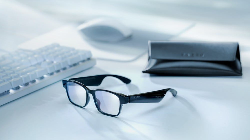 A pair of smart glasses next to a case.