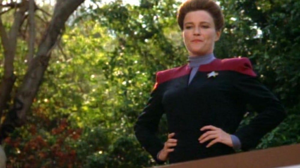 Captain Janeway, looking over a balcony.