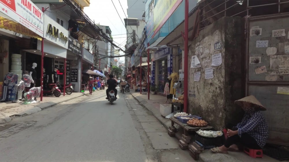 Walking down an alleyway with motorcycles and vendors in Vietnam