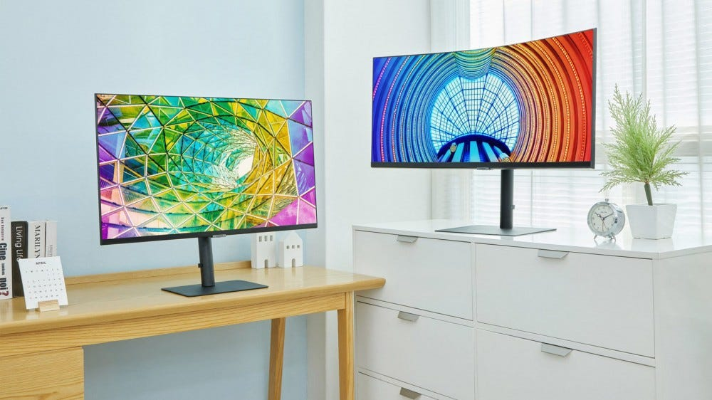 Two new Samsung monitors on a wooden desk and metal filing cabinet