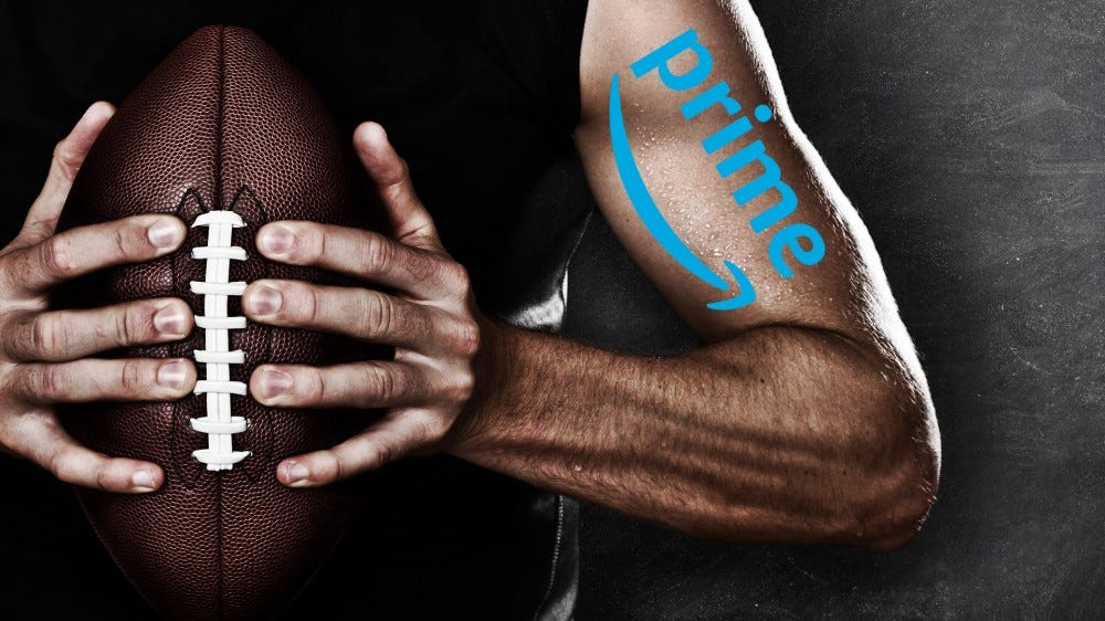 A man holding a football with an Amazon Prime tattoo on his arm.