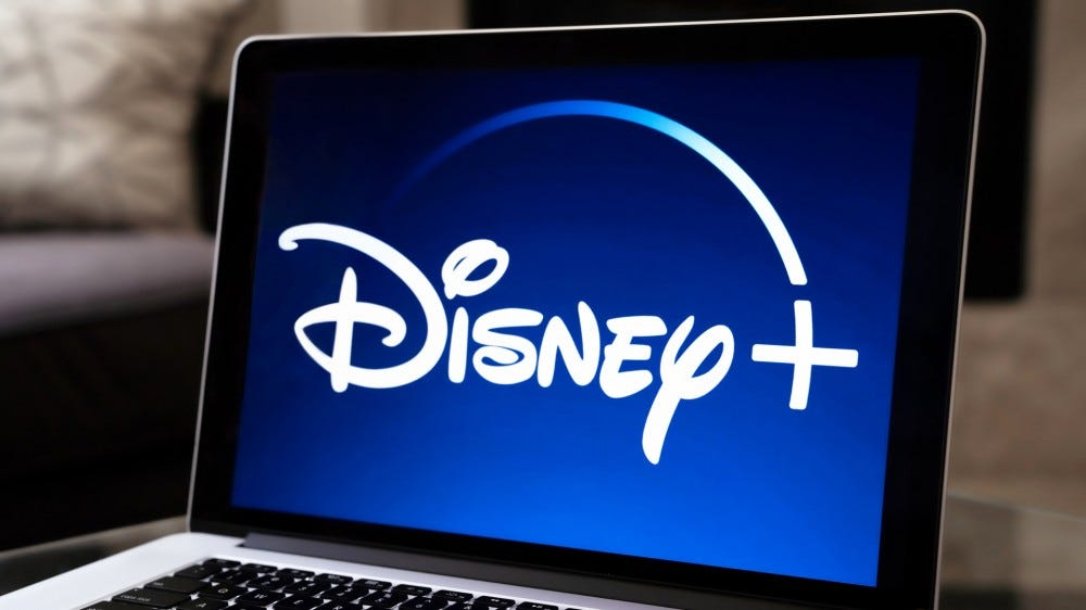 Disney+ logo open on Apple laptop on table next to bowl of popcorn