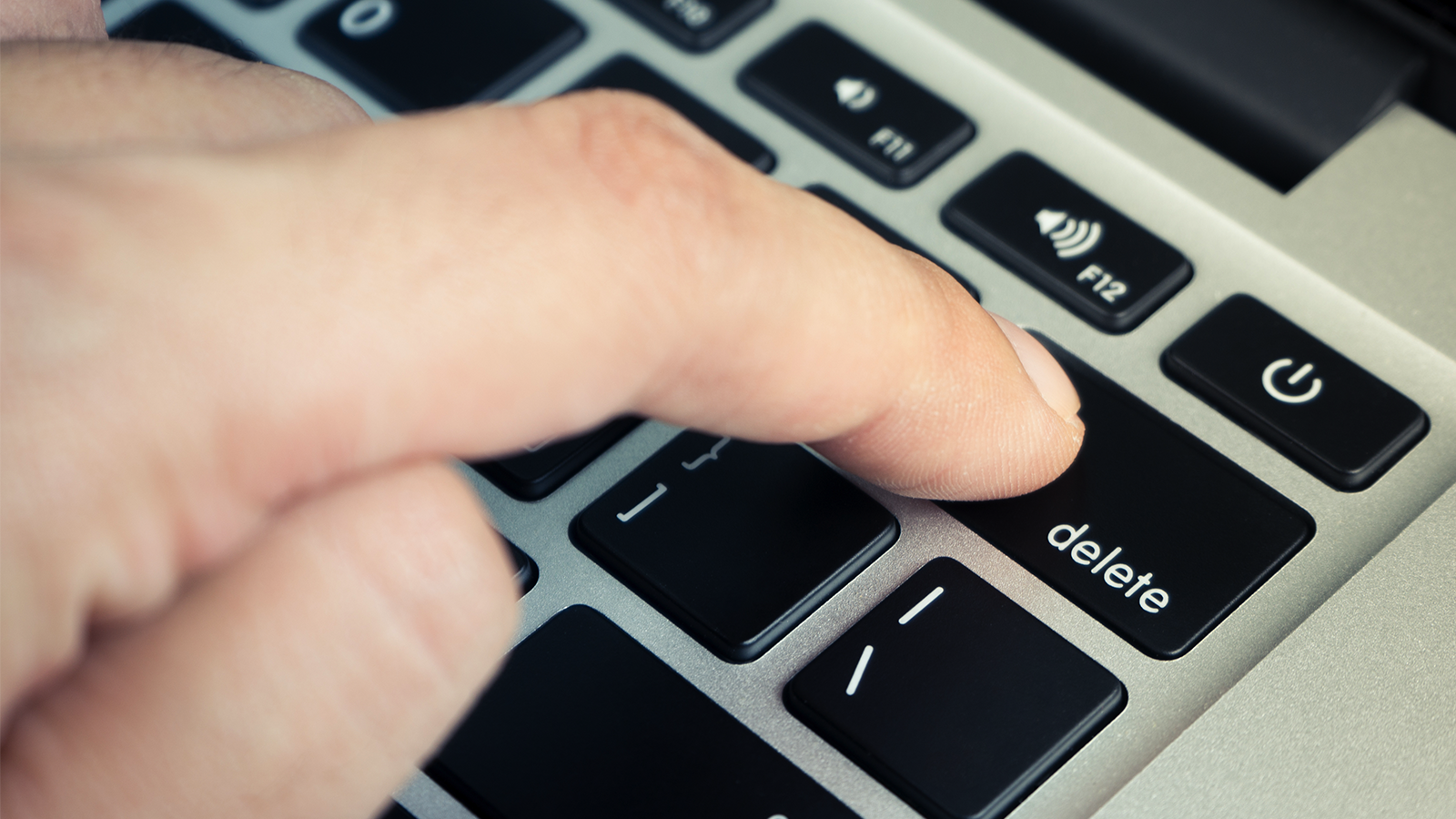 "A finger pushing the ""delete"" key on a keyboard."