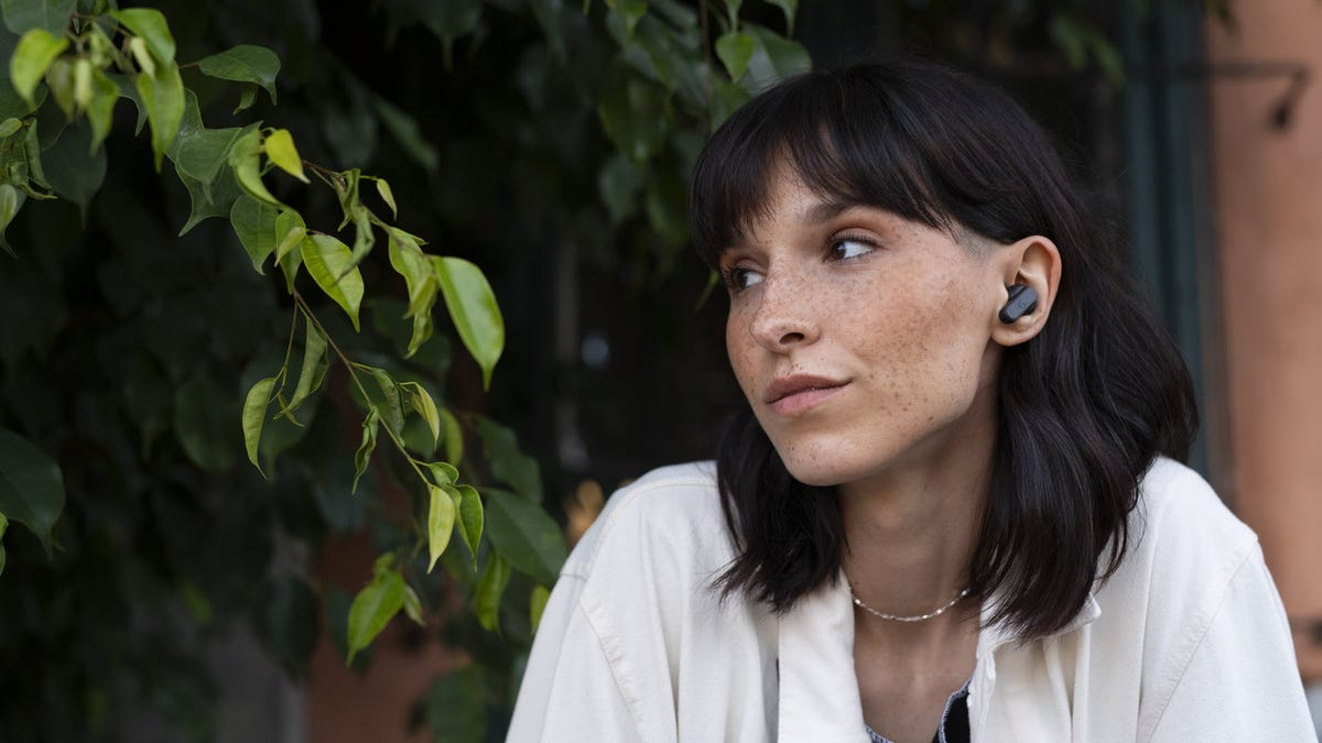 A woman wearing a pair of black true wireless earbuds.