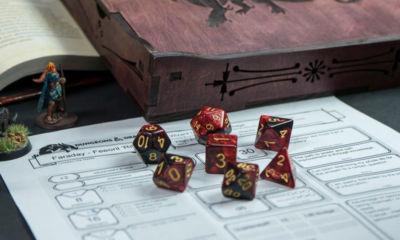Set of red Dungeons & Dragons dice by a miniature and game character sheet