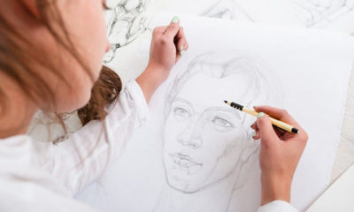 Artist drawing pencil portrait close-up.