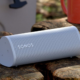A Sonos Roam speaker on a log, next to a mug.