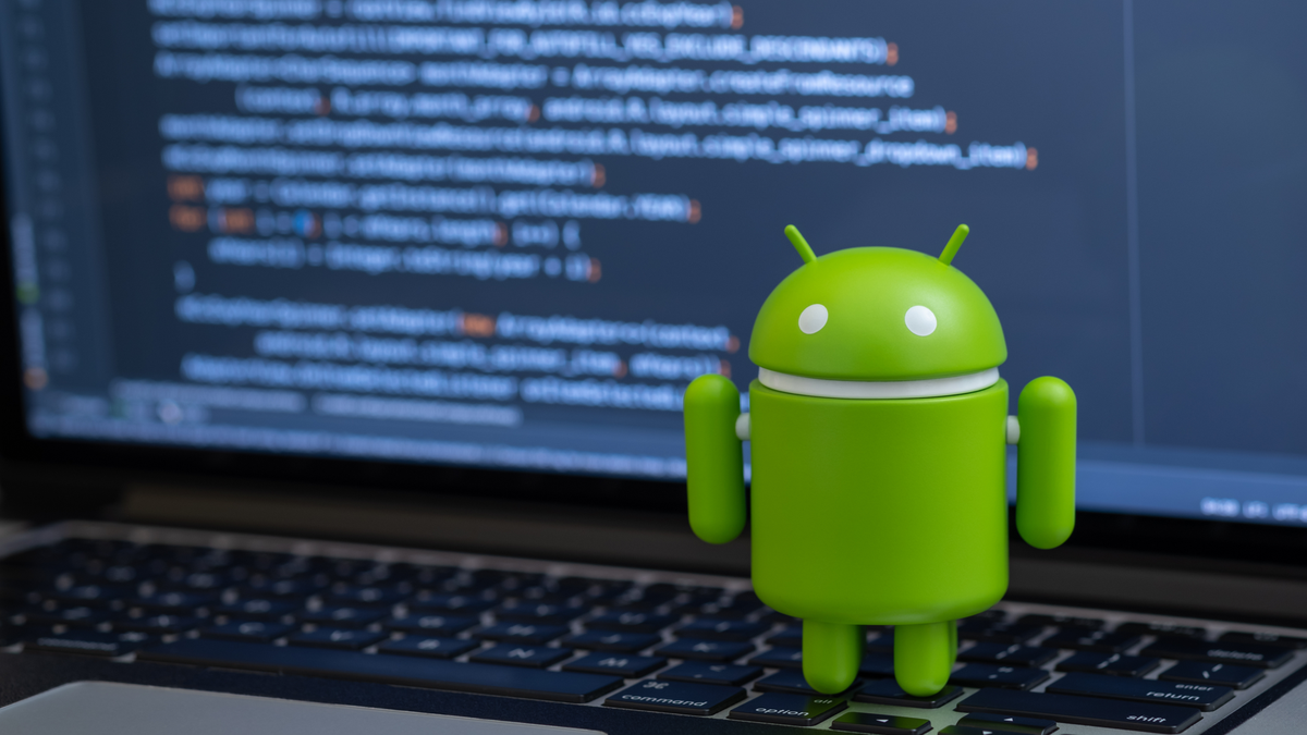 Google Android figure standing on laptop keyboard with code in background