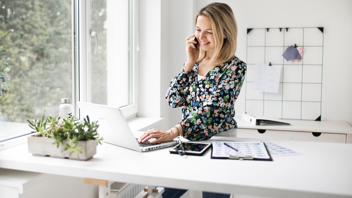 Businesswoman using phone while working at ergonomic standing desk