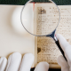 A museum worker wearing white gloves holding a magnifying glass inspects a manuscript or book