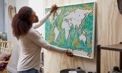 Person mounting their completed LEGO Art World Map set to the wall in a room with worldly decorations