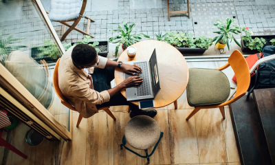 Person working on the Acer Swift X laptop in a café setting