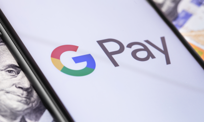 Cash across multiple currencies with smartphone on top featuring Google Pay app logo