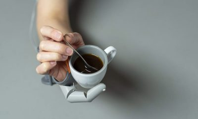 A hand with two thumbs, holding a mug and stirring coffee.