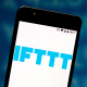 Logo of IFTTT (If This Then That) service on smartphone against blue background with numbers