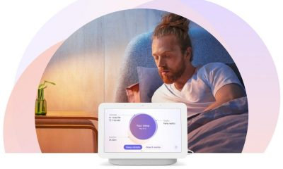 The second generation Nest Hub showing the sleep sensing features. A man in the background getting ready for bed. He has a man bun.