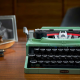 LEGO Typewriter on wooden desk with framed photo and chair behind it