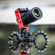 A photo of the Joby Vert bracket paired with a tripod and compact mirrorless camera.