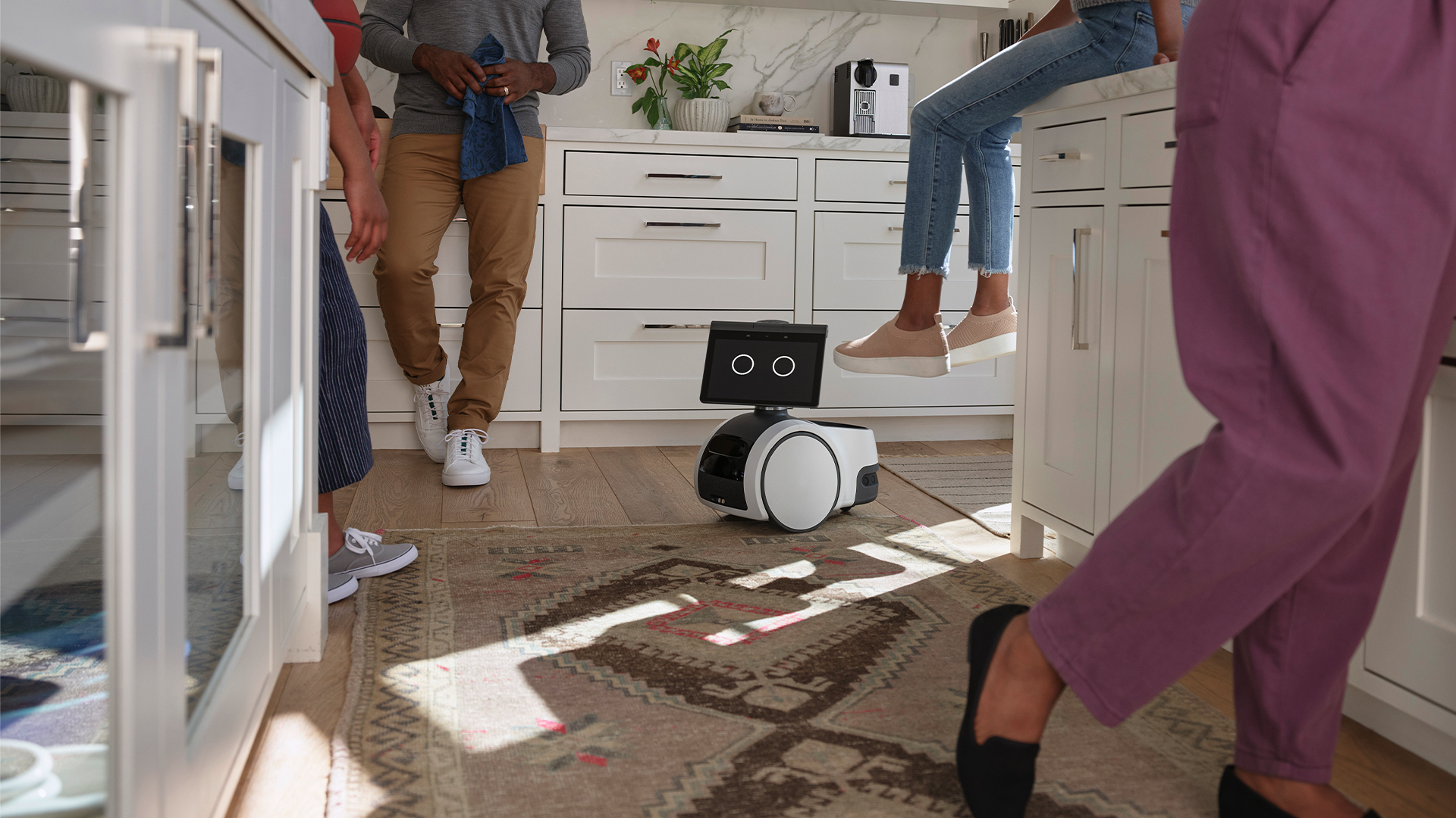 Amazon Astro rolling through a group of people in a kitchen.